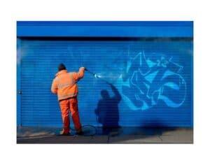 Uomo che applica vernice antigraffiti su saracinesca