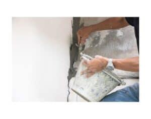 Uomo che ripara crepe nei muri